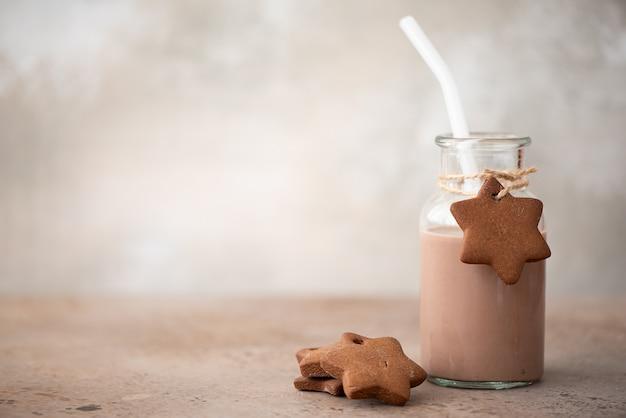 Milkshake de chocolate em garrafa de vidro com biscoitos de gengibre esfarelados na mesa