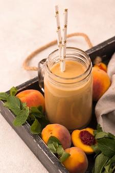 Milkshake de pêssego em ângulo alto com canudos