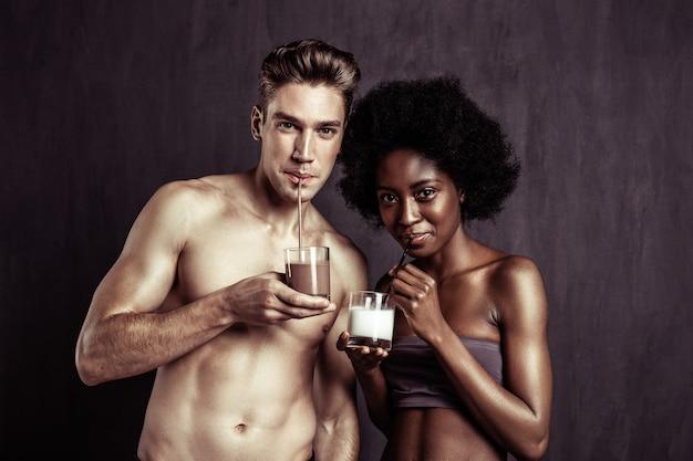 Milkshake delicioso. casal alegre e positivo olhando para você enquanto toma seus coquetéis