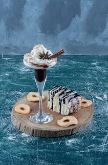 Milkshake e um pedaço de bolo sobre o fundo azul. foto de alta qualidade