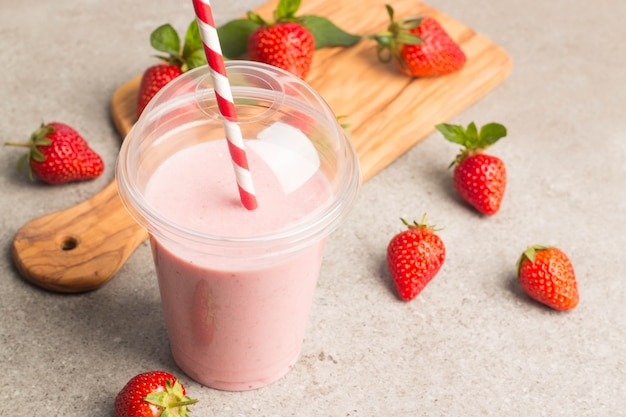 Milkshake fresco, smoothie e morangos frescos em e fundo de madeira. conceito de bebida saudável