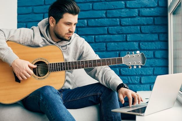 Millenial com guitarra sentado em apartamento de design moderno e usando laptop