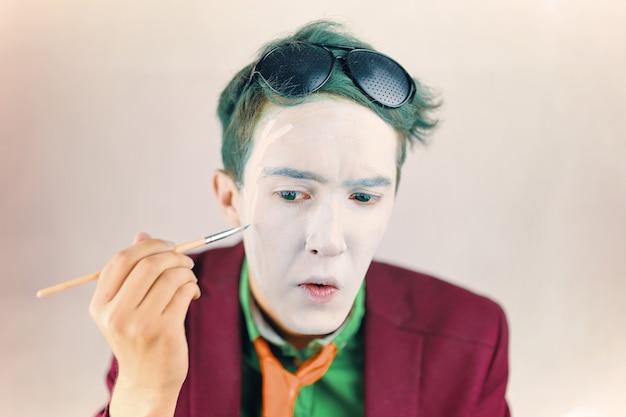 Mim está se preparando para performance cosplayer pinta o rosto com pincel ator com maquiagem branca e gr ...