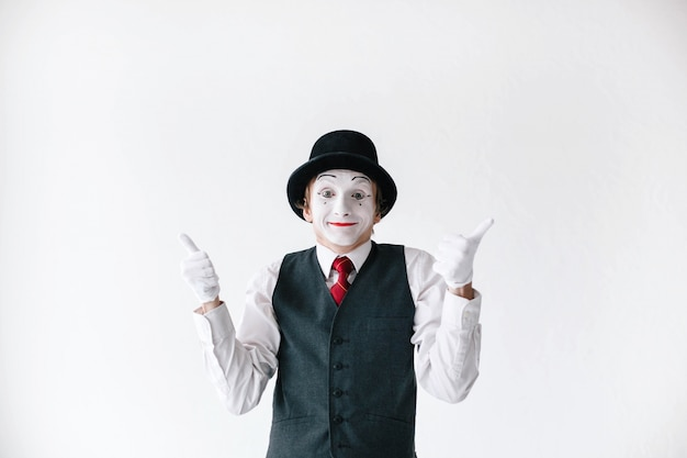 Mime engraçado no chapéu preto mantém seus polegares acima