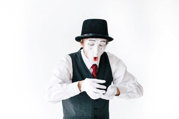 Mime engraçado no chapéu preto olha em algo invisível em seus braços