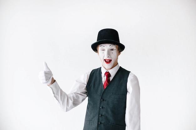 Mime engraçado no chapéu preto prende seu polegar acima