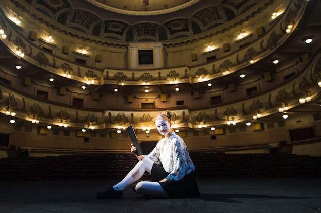 Mime feminino, com, manuscrito, sentando, em, vazio, auditório