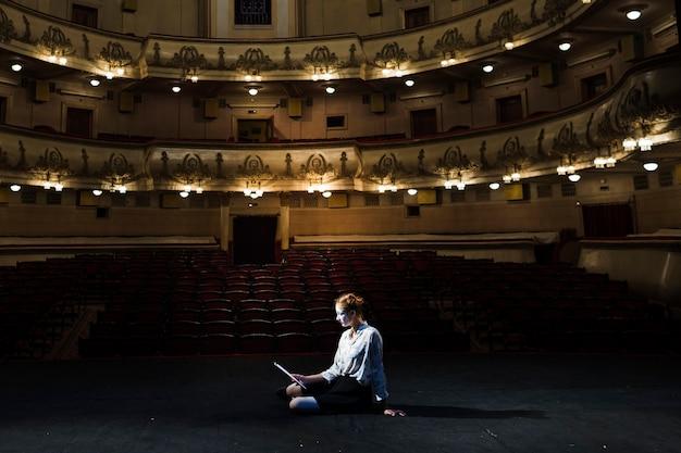 Mime lendo manuscrito no palco no auditório vazio