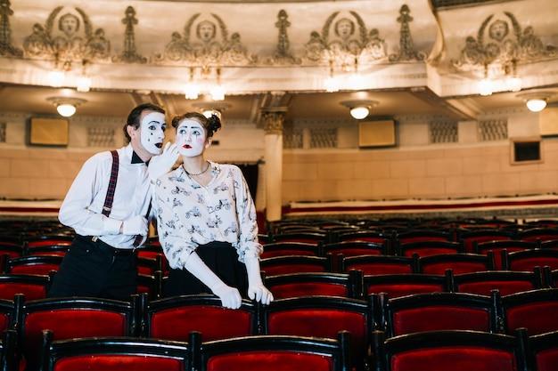 Mime masculino sussurrando no ouvido do mime feminino no auditório