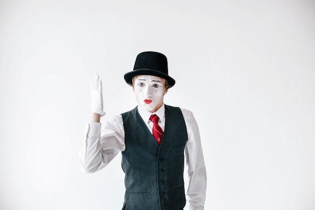 Mime no chapéu preto segura sua mão acima como uma pupila