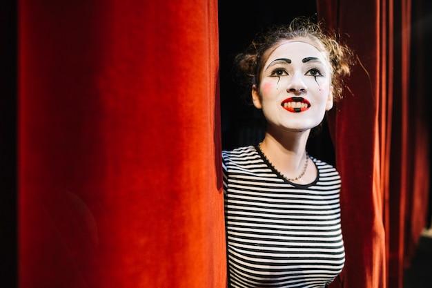 Mime pensativo artista feminino em pé perto da cortina vermelha