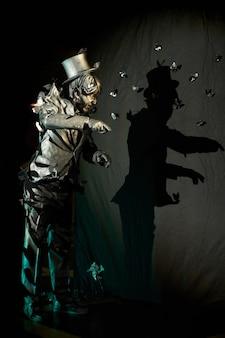 Mímico proficiente que parece uma estátua em pé sobre uma parede de fundo preto com sua sombra. conceito de ato de pantomima espetacular