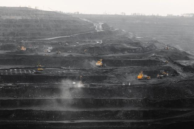 Mina a céu aberto, carregamento de carvão em caminhões, transporte e logística