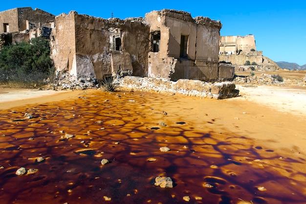 Mina abandonada e suas instalações agora meio demolidas e com lago seco
