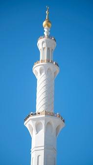 Minarete da mesquita branca no fundo do céu azul