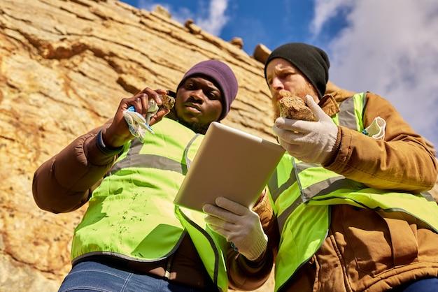 Mineiros, inspecionando o local de trabalho em busca de minerais