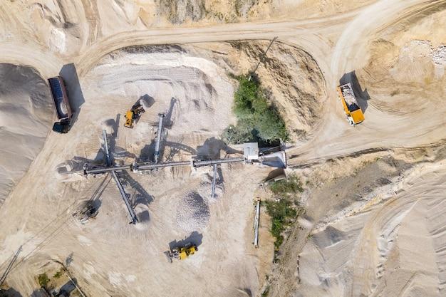 Mineração a céu aberto de materiais de pedra de areia de construção com escavadeiras e caminhões basculantes na correia transportadora.