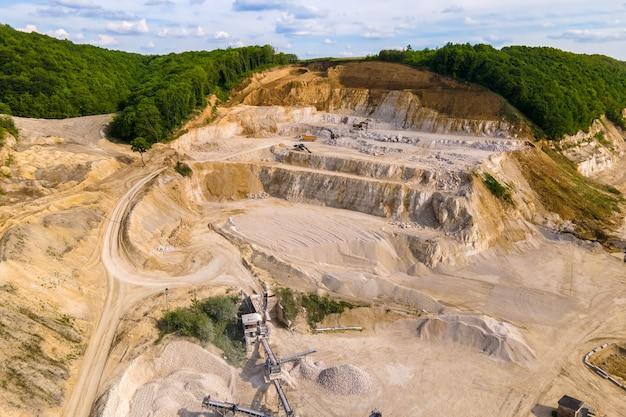 Mineração a céu aberto de materiais de pedra e areia de construção com escavadeiras e caminhões basculantes.