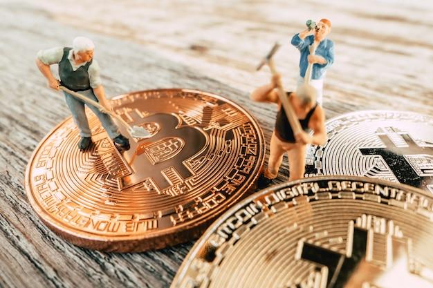 Mineração de bitcoin pessoas em miniatura cavando no valioso fundo madeira de moeda