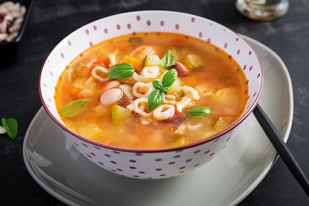 Minestrone, sopa de vegetais italiana com macarrão na mesa escura.