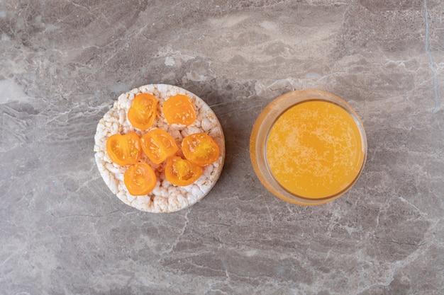 Mingau com fatias de tomate em um copo ao lado de suco de laranja, na superfície de mármore