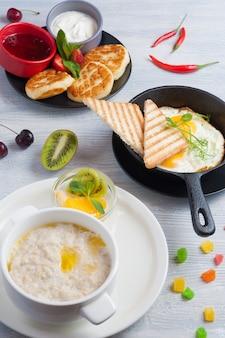 Mingau com frutas, ovos mexidos, cheesecakes. conceito: breakfast