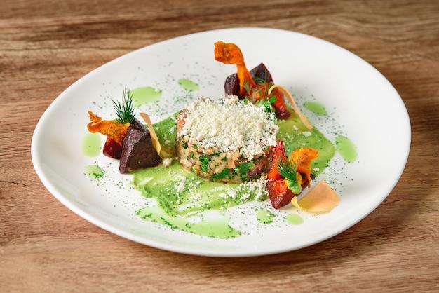 Mingau com legumes e molho pesto polvilhado com queijo. comida de restaurante linda, saborosa e saudável