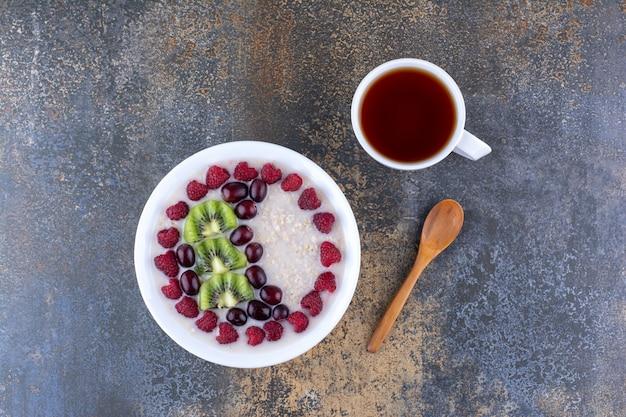 Mingau com leite com frutas, frutas vermelhas e um copo de bebida
