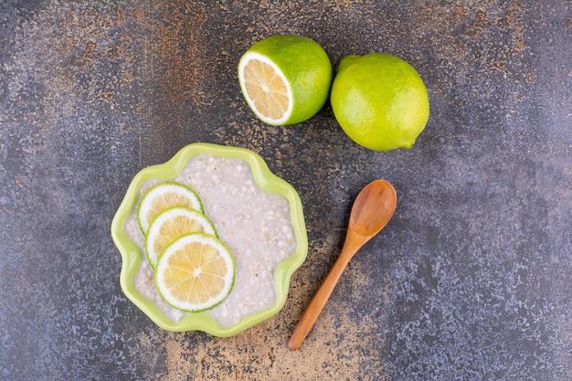 Mingau com leite com rodelas de limão em uma tigela verde