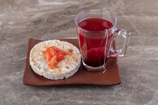 Mingau com rodelas de tomate em um copo sobre uma placa de madeira, na superfície de mármore