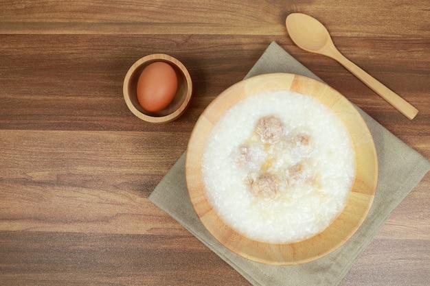 Mingau de arroz com almôndega, ovo e colher na mesa de madeira