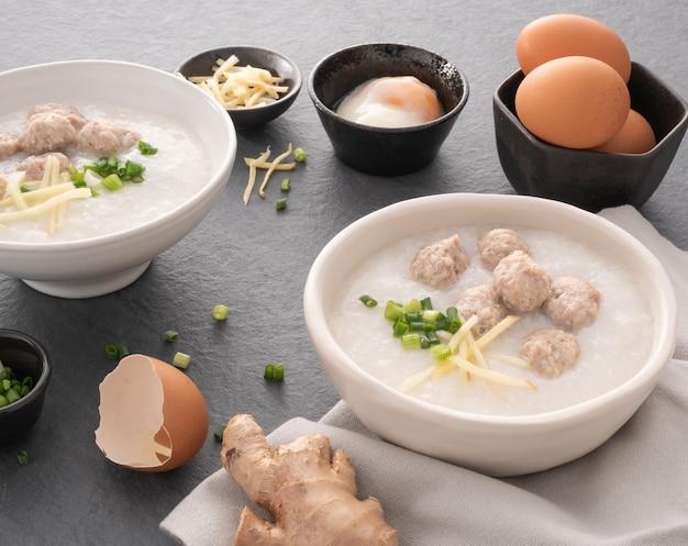 Mingau de arroz com carne de porco picada em tigela branca. tigela de mingau de arroz com ovo cozido macio. café da manhã asiático