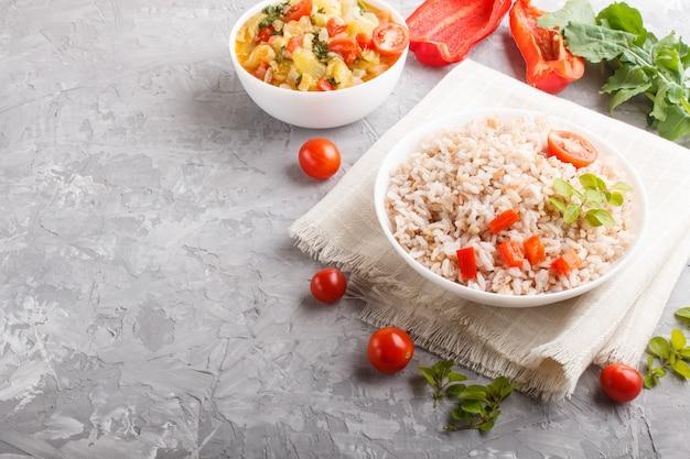 Mingau de arroz não polido com legumes cozidos e orégano em tigela branca sobre um fundo cinza de concreto