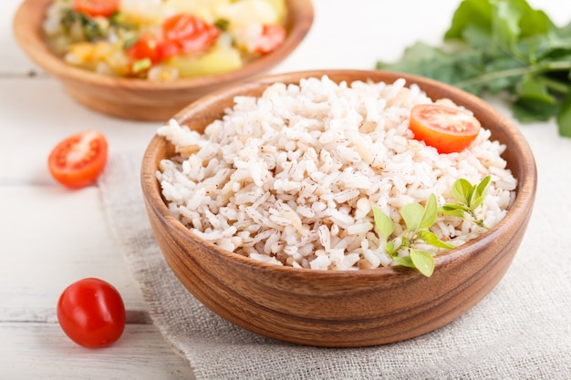 Mingau de arroz não polido com legumes cozidos e orégano em uma tigela de madeira sobre um fundo branco de madeira