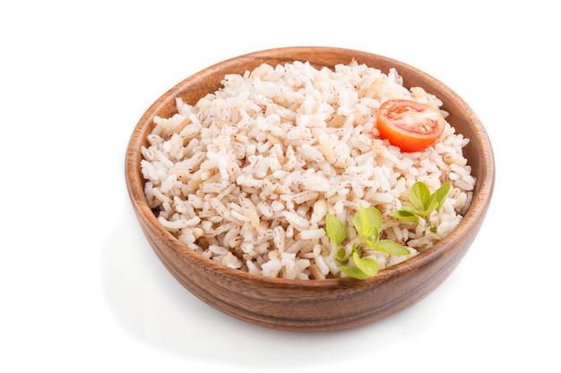 Mingau de arroz não polido na tigela de madeira, isolada no fundo branco
