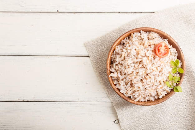 Mingau de arroz não polido na tigela de madeira sobre um fundo branco de madeira