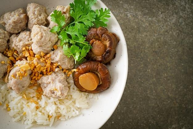 Mingau de arroz seco caseiro com tigela de porco cozido