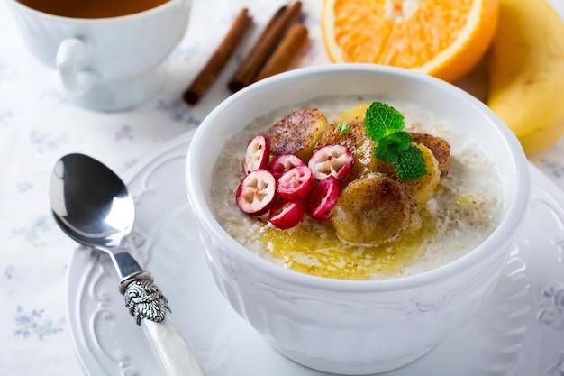 Mingau de aveia com banana assada, canela, laranja e cranberries em uma tigela de cerâmica sobre uma superfície clara. foco seletivo.
