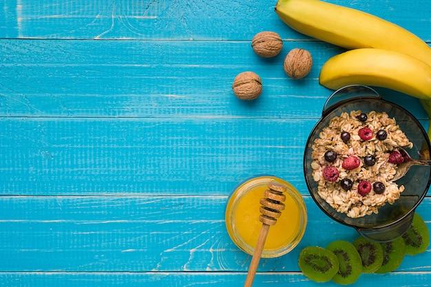 Mingau de aveia com banana, kiwi, nozes e mel em uma tigela com ovo no café da manhã saudável em fundo de madeira rústico. alimentos saudáveis no café da manhã. vista do topo. copie o espaço