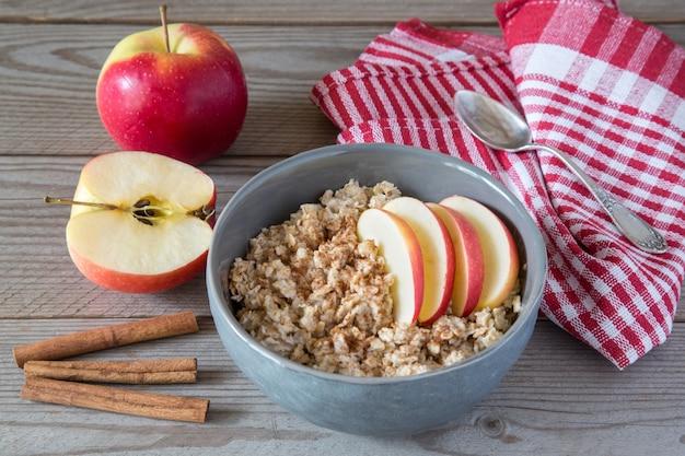 Mingau de aveia com maçãs e canela em uma mesa de madeira