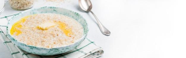 Mingau de aveia com manteiga em um prato de cerâmica sobre um fundo claro de pedra ou concreto. foco seletivo