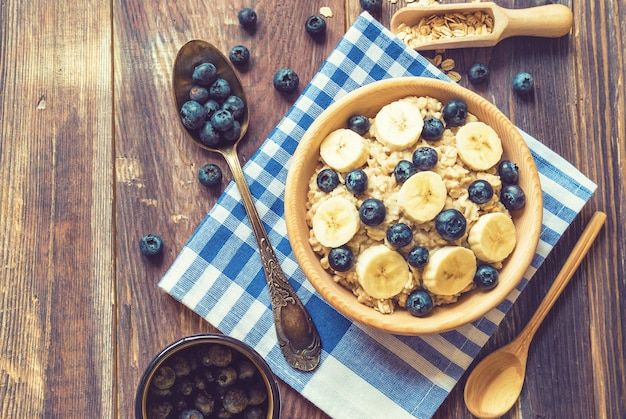 Mingau de aveia com mirtilos e banana em uma tigela de madeira com fundo de madeira rústico café da manhã saudável
