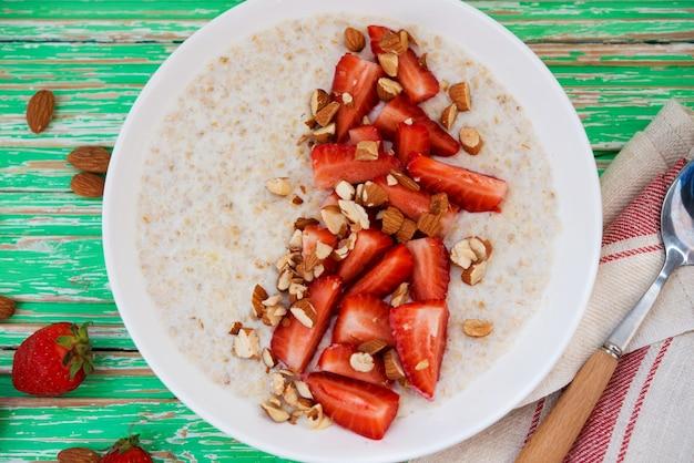 Mingau de aveia com morangos e amêndoas em um prato branco sobre fundo rústico, close-up