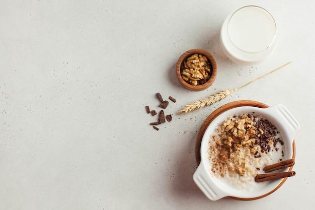 Mingau de aveia com nozes, canela e chocolate, um copo de leite