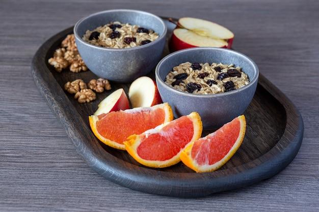 Mingau de aveia com passas, maçãs, laranjas e nozes em uma mesa de madeira