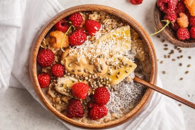 Mingau de aveia com sementes de chia, bagas, manteiga de amendoim e sementes de cânhamo na tigela de madeira, fundo branco.