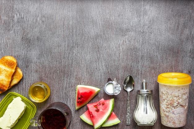 Mingau de aveia com torrada de melancia com manteiga e mel em uma mesa de madeira o conceito de uma pausa saudável ...