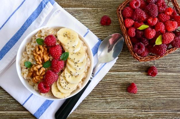 Mingau de aveia deliciosa e saudável com banana, framboesas, nozes. café da manhã saudável. comida de fitness. nutrição apropriada. postura plana. vista do topo.