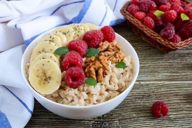 Mingau de aveia deliciosa e saudável com banana, framboesas, nozes. café da manhã saudável. comida de fitness. nutrição apropriada.