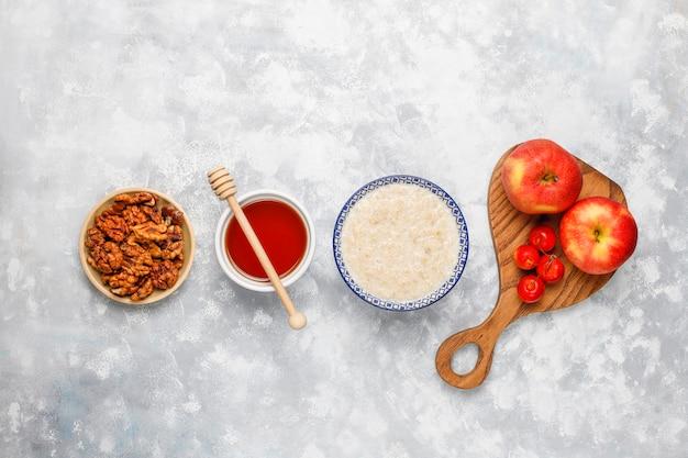 Mingau de aveia em uma tigela com fatias de maçã vermelha e mel, vista superior